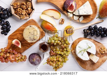 Cheese plate with blue cheese brie truffle hard cheese with grapes figs pears honey fruits and nuts on white table. Top view.