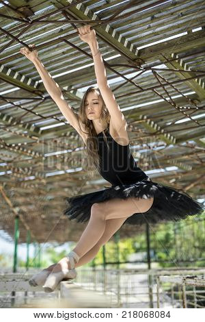 Beautiful ballerina with closed eyes hangs on her hands on the awning and reclines on the metal handrail with her feet on the concrete pier. She wears a black tutu with a leotard. Outdoors. Vertical.