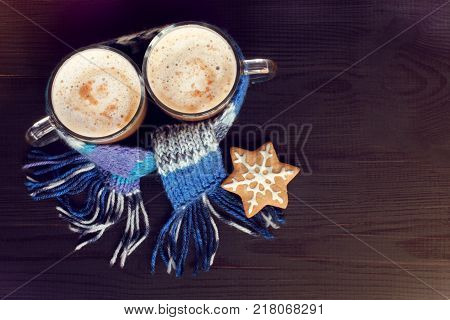 two glass mugs with frothy cappuccino in a blue scarf and gingerbread cookie view from the top / warming the coffeehouse for winter weekend