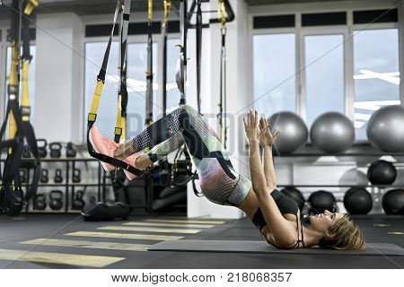 Pretty girl is training with TRX straps in the gym. She leans on her shoulders on the mat while her feet are in the straps in the air. Woman wears colorful pants with black top and pink sneakers.