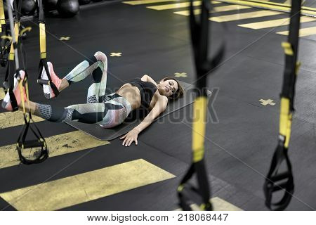 Cute girl is training with TRX straps in the gym. She lies on the fitness mat while her feet are in the straps in the air. Woman wears colorful pants with black top and pink sneakers. Horizontal.