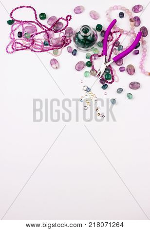 Beading. Rose and emerald bead mix on white background. Glass seed beads gemstones metal rings pliers. Handmade fine arts. Top view. Space for text.