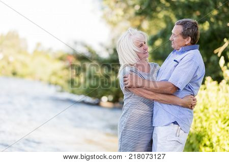 Elderly marriage hugging by the lake. Nature and recreation. Soulmates.