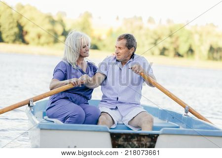 Older couple sailing on a boat. Recreation in the bosom of nature.
