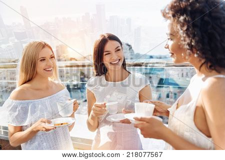 Gossip about boys. Three glad jolly female friends enjoying coffee while gossiping and laughing