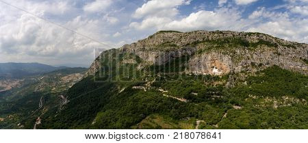 Aerial panorama view with Ostrog Monastery church under tall mountain walls, Montenegro