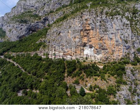 Aerial view on Ostrog Monastery church under tall mountain walls, Montenegro