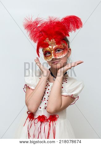 Adorable little girl with Venetian carnival mask on white background