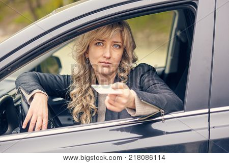 A beautiful woman in the car window shows a driver's license