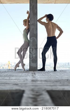 Attractive couple of ballet dancers lean on the concrete wall on the floor of the unfinished building on the cityscape background. Topless guy wears a black dance pants, girl wears a green leotard.