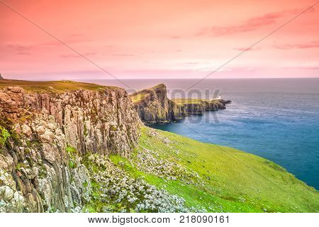Neist Point cliff with Lighthouse on top, located in the Isle of Skye, Highlands in Scotland, United Kingdom at sunset. Neist Point is a very photographed place and tourist attraction on Isle of Skye.