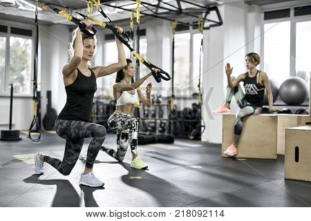 Attractive girls are training with TRX straps in the gym on the windows background. They are wearing the multicolored sportswear: pants, tops, sleeveless and sneakers. Horizontal.