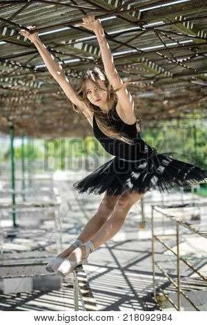 Cute ballerina hangs on her hands on the awning and reclines on the metal handrail with her feet on the concrete pier. She wears a black tutu with a leotard and looks into the camera. Outdoors.
