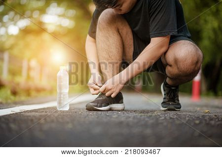 run runner with water and sport shoe road jogging flare sunset asphalt street fitness cross sunbeam success running sportswear.Man tying jogging shoes.A person running outdoors on a sunny day.