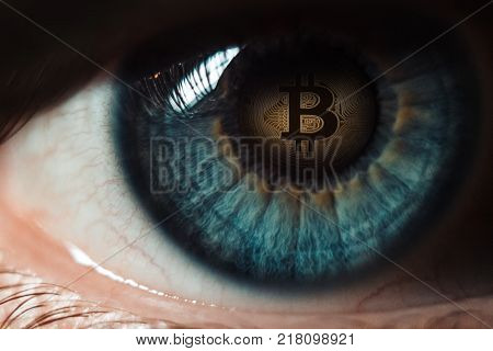 Bitcoin. Eye of a person with the bitcoin coin logo in the pupil