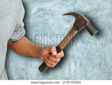 Aggressive human hand holding hammer on concrete background