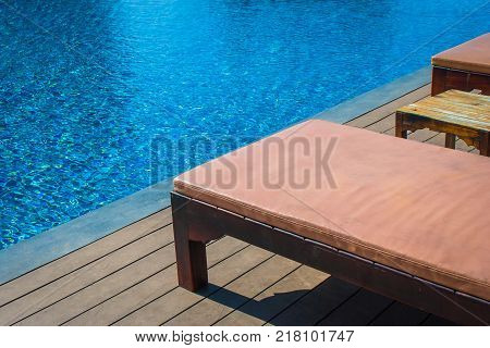 Relaxation Concept : Wooden daybed setting on wooden floor beside swimming pool at the resort.