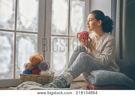 Beautiful young woman sitting by the window and looking at frozen glass. Girl enjoying warm beverage.