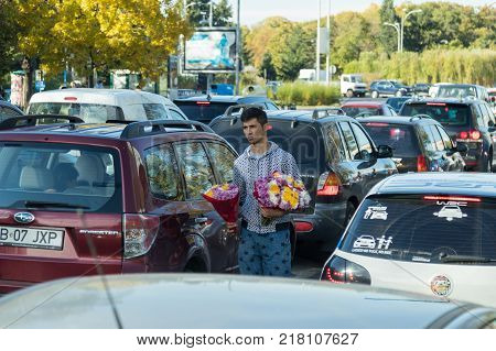 Bucharest Romania October 10 2017 : A young man walks between cars on a busy highway and sells flowers in Bucharest city in Romania