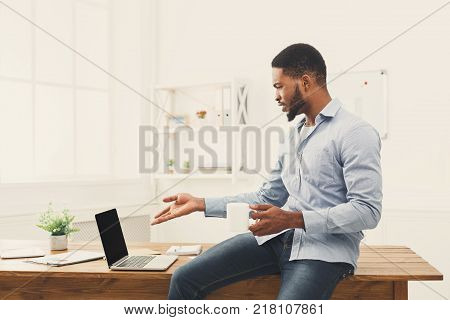 Surprised stressed african-american businessman looking at laptop screen in modern office. Job problems concept, copy space