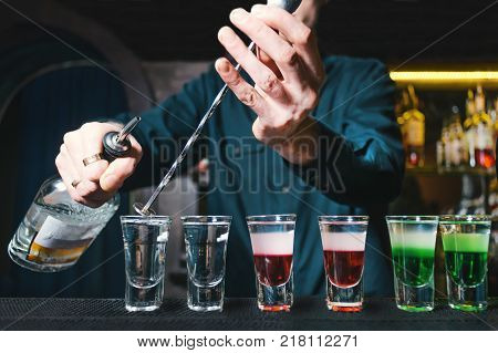 The barman creates alcoholic shots at the bar at the restaurant. The barman pours alcohol into shots. Bartender pouring strong alcoholic drink into small glasses on bar, shots