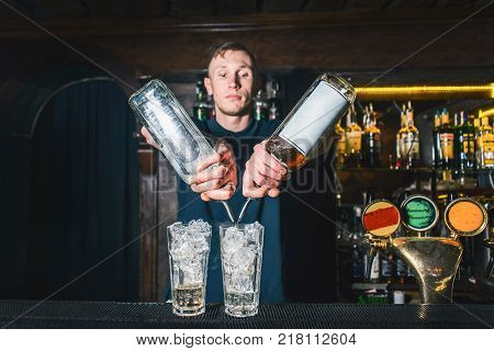 The barman pours alcohol from the bottles into a cocktail. The barman mixes alcohol. Create a cocktail in the bar