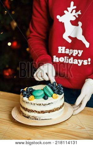 A Girl In A Christmas Red Sweater At Home Prepares A Cake For A Festive Table For A Family Holiday