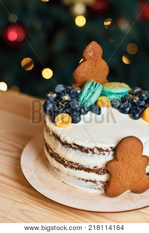 Beautiful Decorated Cake With Gingerbread Men For Christmas Table On New Year Bokeh Background. Prep