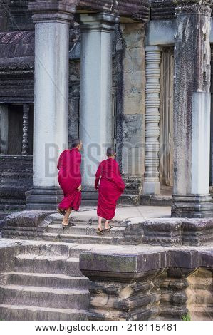 SIEM REAP CAMBODIA - OCT 17 : Budhist monks at the Angkor Wat Temple in Siem Reap Cambodia on October 17 2017 The Angkor Wat is an UNESCO World Herutage site since 1992