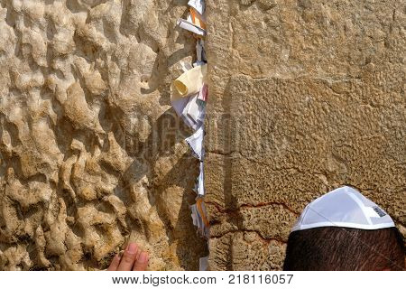 Hand of praying man at the Wailing Wall with notes and wishes Jerusalem.