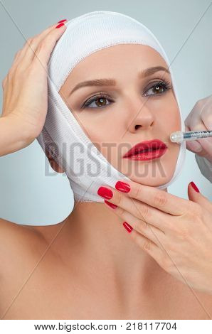 Woman get injection in lips. Beautiful woman after plastic surgery with bandaged face. Beauty. Fashion