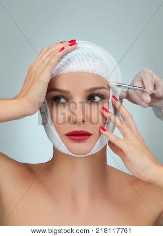 Patient in bandages getting injection over eyebrow.  Beauty, Fashion and Plastic Surgery concept.