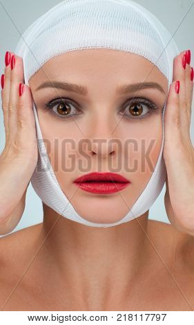 Patient in bandages. Beautiful woman after plastic surgery with bandaged face.