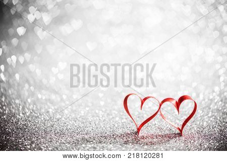 Two ribbon hearts on glowing bokeh lights background