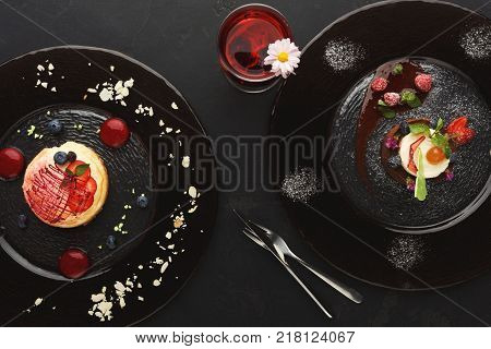 Exquisite restaurant desserts. Chocolate and vanilla souffle and lemon cheesecake with berry spheres on glass plates decorated with fresh berries and mint. Haute cuisine concept, top view