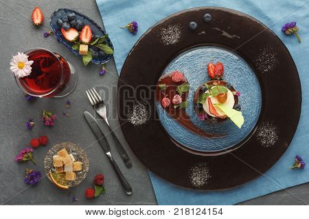 Exquisite restaurant mousse dessert. Chocolate and vanilla souffle on walnut biscuit served at gray table on glass plate finely decorated with fresh berries and mint. Haute cuisine concept, top view