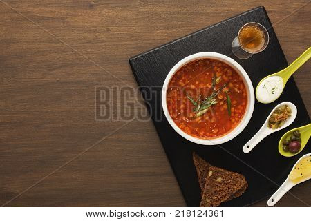 Delicious saltwort with smoked meat, served with rye-bread, assortment of snacks and glass of hard drink. Traditional russian meals in modern restaurant serving, top view, copy space