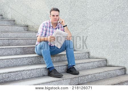 Portrait of serious young man sitting on stairs, holding newspaper and making call searching for job. Unemployment and job search concept
