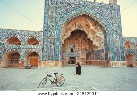 ISFAHAN, IRAN - OCT 14, 2017: Women walking past a historical persian mosque with beautiful artworks on October 14, 2017. The 3rd largest city of Iran Isfahan is outstanding example of Islamic culture
