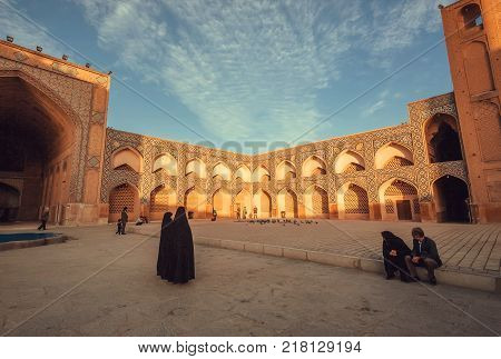 ISFAHAN, IRAN - OCT 14, 2017: Women in dark muslim dress walking past a historical persian mosque with courtyard on October 14, 2017. The 3rd largest city of Iran Isfahan is an example of Islamic culture