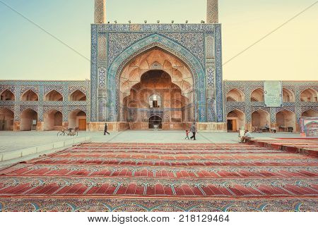 ISFAHAN, IRAN - OCT 14, 2017: Persian carpets at the entrance of the historical iranian mosque with artworks on October 14, 2017. The 3rd largest city of Iran Isfahan is an example of Islamic culture