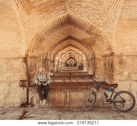 ISFAHAN, IRAN - OCT 14, 2014: Under famouse persian Pol-e Khaju bridge and elderly active man reading a book on October 14, 2014. The 3rd largest city of Iran Isfahan is an example of Islamic culture