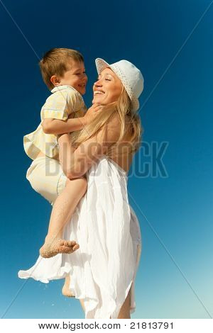 Boy flying on his mother's hands at beach