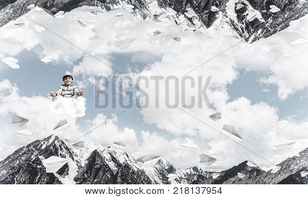 Young little boy keeping eyes closed and looking concentrated while meditating on cloud among flying paper planes and between two nature worlds.