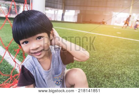Shy boy is sitting next to soccer goal in practice field