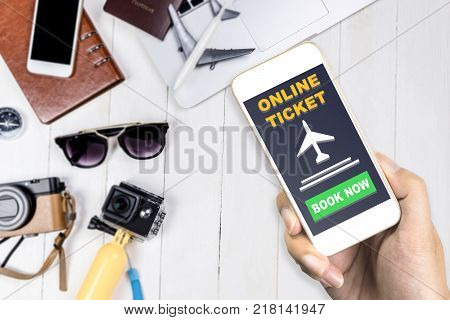 Traveler is using his mobile phone to book flight ticket