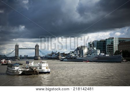 HMS Belfast and Tower Bridge under moody skies