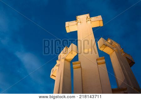 Vilnius, Lithuania. Famous White Monument Three Crosses On The Bleak Hill In Lighting In Evening Or Night Illumination. Bottom View