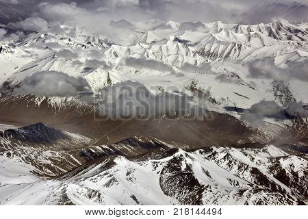 Mountain valley, winter landscape in the high Himalayas, the valley stretches among the snow capped mountain peaks.