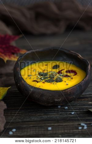 Homemade pumpkin cream soup with pumpkin seeds and pumpkin oil on a dark wooden background. Rustic style